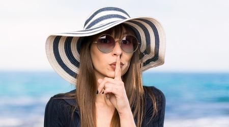 Young woman in bikini doing silence gesture at the beach