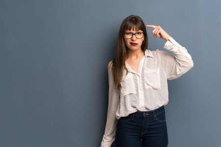 Woman with glasses over blue wall making the gesture of madness putting finger on the head