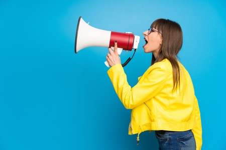 Young woman with yellow jacket on blue background shouting through a megaphone Stockfoto
