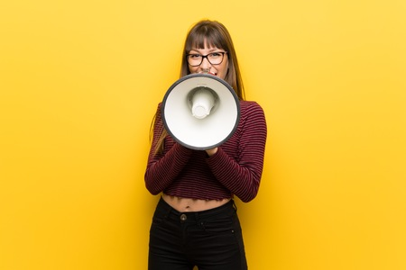 Woman with glasses over yellow wall shouting through a megaphone