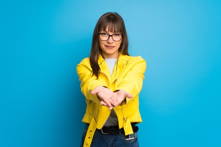 Young woman with yellow jacket on blue background holding copyspace imaginary on the palm to insert an ad