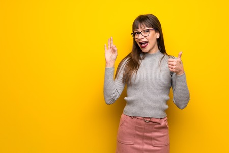 Woman with glasses over yellow wall showing ok sign with and giving a thumb up gesture Imagens - 119795240