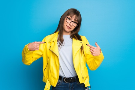Young woman with yellow jacket on blue background proud and self-satisfied in love yourself concept Archivio Fotografico