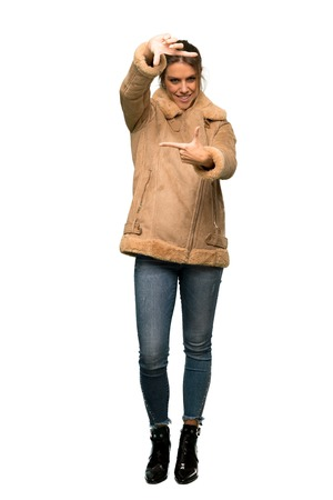 A full-length shot of a Blonde woman with a coat focusing face. Framing symbol over isolated white background