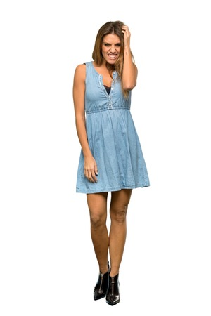 A full-length shot of a Blonde woman with jean dress having doubts over isolated white background Stock Photo