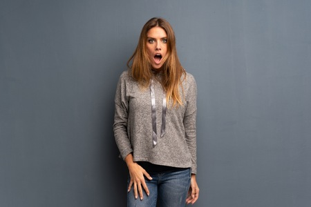 Blonde woman over grey background with surprise facial expression Foto de archivo