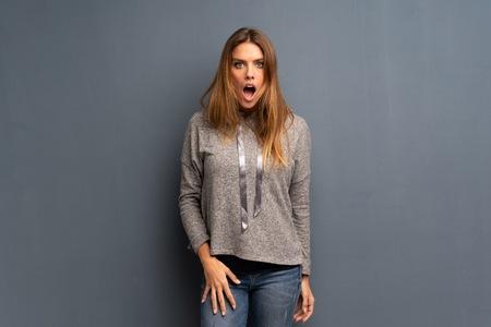 Donna bionda su sfondo grigio con espressione facciale a sorpresa
