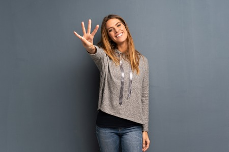 Blonde woman over grey background happy and counting four with fingers Imagens