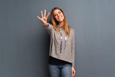 Donna bionda su sfondo grigio felice e contando quattro con le dita