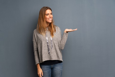 Blonde woman over grey background presenting an idea while looking smiling towards