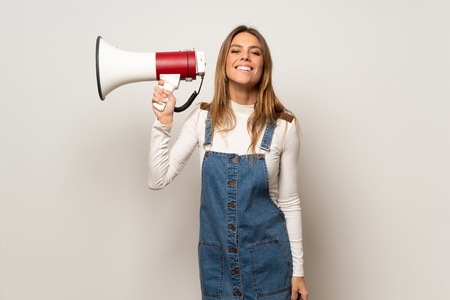 Beautiful woman over isolated white wall holding a megaphone Imagens