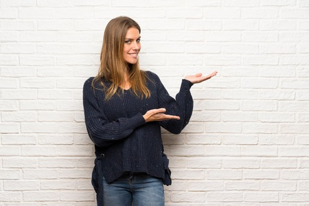 Blonde woman over brick wall extending hands to the side for inviting to come
