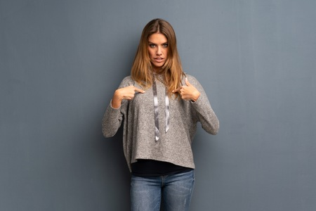 Blonde woman over grey background with surprise facial expression Фото со стока