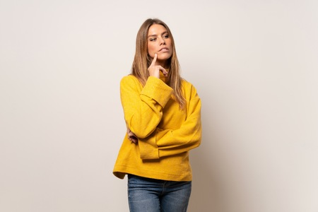 Woman with yellow sweater over isolated wall thinking an idea while looking up