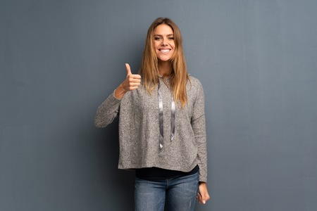 Blonde woman over grey background giving a thumbs up gesture and smiling