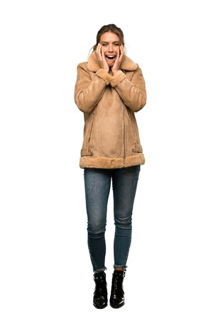 A full-length shot of a Blonde woman with a coat nervous and scared stretching hands to the front over isolated white background Stock Photo