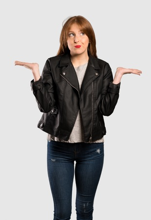 Young redhead woman having doubts while raising hands over isolated grey background Stock Photo