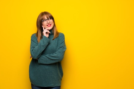 Woman with glasses over yellow wall thinking an idea while looking up Stock Photo