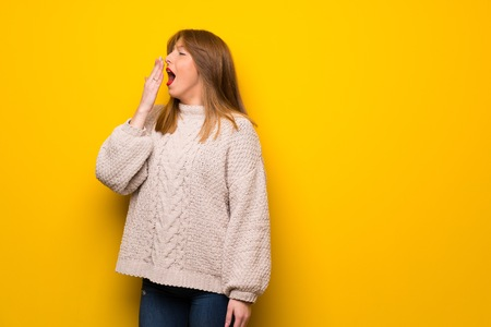 Redhead woman over yellow wall yawning and covering wide open mouth with hand