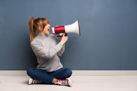 Roodharige vrouw die op de grond zit te schreeuwen door een megafoon Stockfoto