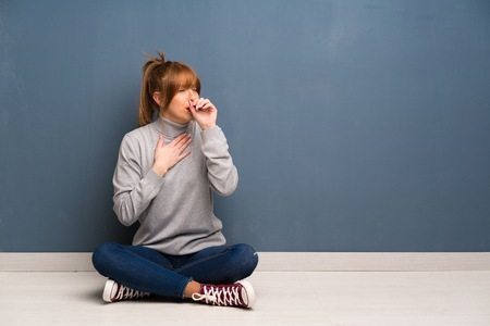 Redhead woman siting on the floor is suffering with cough and feeling bad