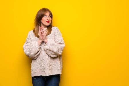 Redhead woman over yellow wall scheming something Фото со стока