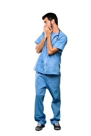 Disparo de cuerpo entero del médico cirujano hombre nervioso y asustado poniendo las manos a la boca sobre fondo blanco aislado