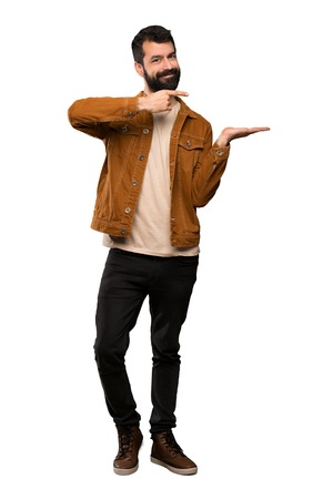 Handsome man with beard holding copyspace imaginary on the palm to insert an ad over isolated white background 版權商用圖片