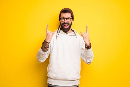 Hippie man with dreadlocks making rock gesture