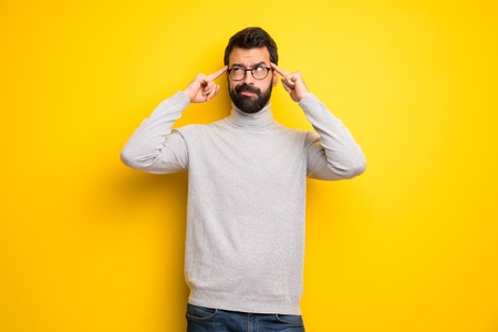 Man with beard and turtleneck having doubts and thinking Foto de archivo