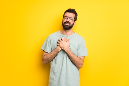 Man with beard and green shirt having a pain in the heart