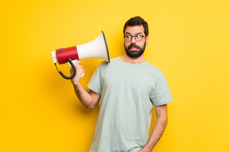 Man with beard and green shirt taking a megaphone that makes a lot of noise Imagens