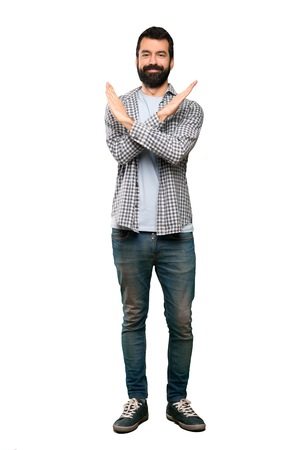 Handsome man with beard making NO gesture over isolated white background