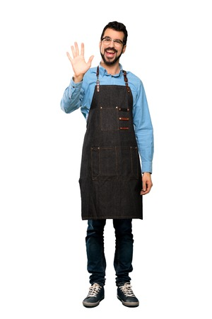 Full-length shot of Man with apron saluting with hand with happy expression over isolated white background