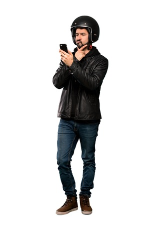 Full-length shot of Biker man thinking and sending a message over isolated white background