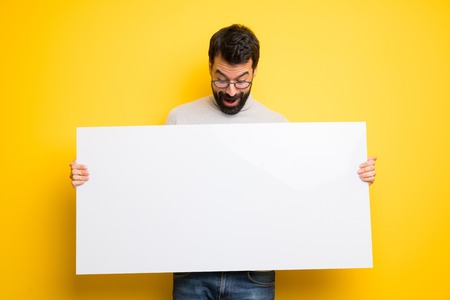 Man with beard and turtleneck holding a placard for insert a concept Imagens