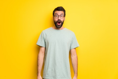 Man with beard and green shirt with surprise and shocked facial expression