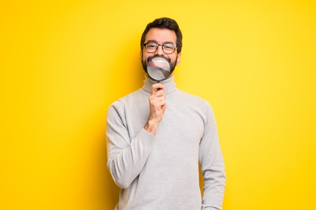 Man with beard and turtleneck taking a magnifying glass and showing teeth through it