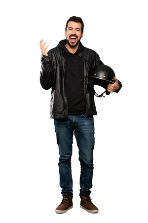 Full-length shot of Biker man smiling a lot over isolated white background