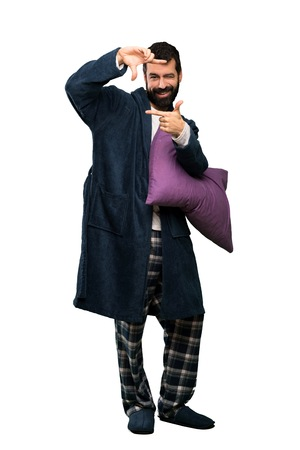 Man with beard in pajamas focusing face. Framing symbol over isolated white background