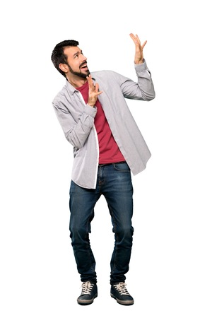 Full-length shot of Handsome man with beard nervous and scared over isolated white background