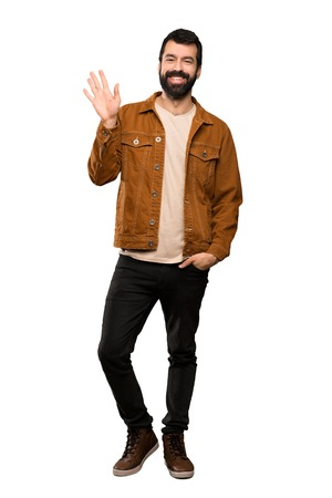 Handsome man with beard saluting with hand with happy expression over isolated white background