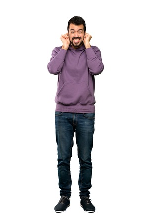 Full-length shot of Handsome man with sweatshirt frustrated and covering ears over isolated white background