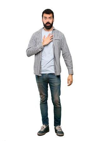 Handsome man with beard surprised and shocked while looking right over isolated white background