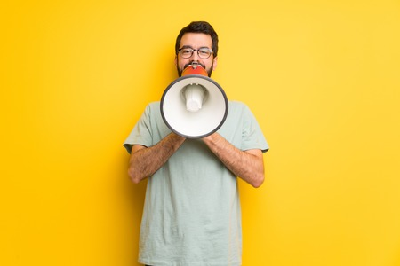 Man with beard and green shirt shouting through a megaphone to announce something
