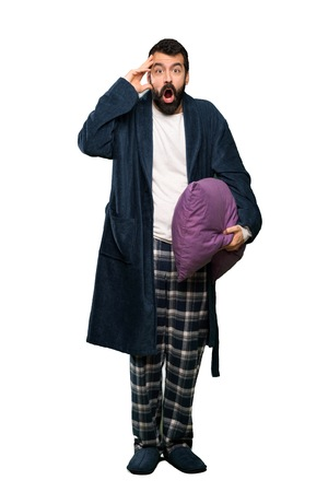 Man with beard in pajamas with surprise expression over isolated white background