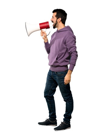 Full-length shot of Handsome man with sweatshirt shouting through a megaphone over isolated white background Imagens
