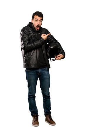 Full-length shot of Biker man surprised and pointing side over isolated white background