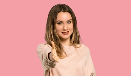 Teenager girl with pink sweater shaking hands for closing a good deal over isolated pink background