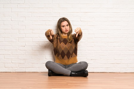 Teenager girl sitting on the floor showing thumb dowg with negative expression Banco de Imagens